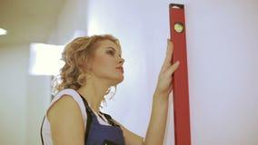 Schöne junge Frau mit messender Wand des Geistniveaus im neuen Haus stock footage