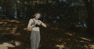 Schöne junge Frau mit MP3-Player hörend auf Melodien und Betrieb im Stadtpark lizenzfreie stockbilder