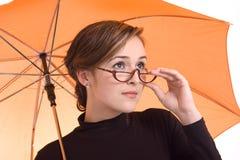 Schöne junge Frau mit orange Regenschirm Stockfotos