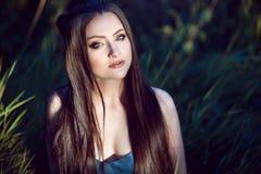 Schöne junge Frau mit perfektem bilden und lang das seidige gerade Haar, das auf dem Gebiet sitzt stockfotografie