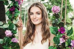 Schöne junge Frau mit Rose Flowers Outdoors stockfoto