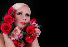 Schöne junge Frau mit roten Rosen und rosa Iris in ihrem Haar über Schwarzem Stockfoto