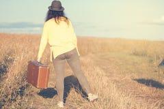 Schöne junge Frau mit schwarzem Hut trägt braunen Weinlesekoffer im Feldweg während des Sommersonnenuntergangs Rückseitige Ansich lizenzfreies stockfoto
