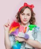 Schöne junge Frau mit Stift-obenmake-up und -frisur mit Reinigungswerkzeugen auf rosa Hintergrund lizenzfreie stockfotos