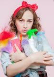 Schöne junge Frau mit Stift-obenmake-up und -frisur mit Reinigungswerkzeugen auf rosa Hintergrund stockfotos