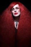 Schöne junge Frau mit stilvollem gotischem Make-up und langem Rot h Stockbild