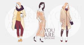 Schöne junge Frau mit Tendenzfrisur in einer Modejacke, Hosen in den Gläsern mit Kaffee Auch im corel abgehobenen Betrag Lizenzfreie Stockbilder