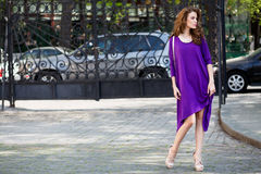 Schöne junge Frau mit violettem Kleid Stockbild