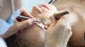 Schöne junge Frau mit Wimpererweiterung Frauenauge mit den langen Wimpern Kosmetikerwimpererweiterung für Junge stock video