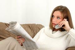 Schöne junge Frau mit Zeitung und Mobiltelefon Lizenzfreie Stockbilder