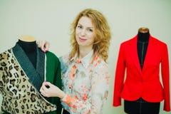 Schöne junge Frau näht Designermantel Leoparddruckmantel und -GRÜN stockbild