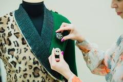 Schöne junge Frau näht Designermantel Leoparddruckmantel und -GRÜN lizenzfreies stockbild
