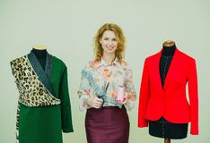 Schöne junge Frau näht Designermantel Leoparddruckmantel und -GRÜN stockfoto