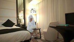 Schöne junge Frau nach Dusche mit einem Tuch auf ihrem Kopf im weißen Mantel setzt sich im Lehnsessel zu Hause oder im Hotelzimme stock footage