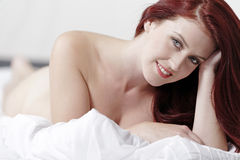 Frau nackt auf Bett Stockbild