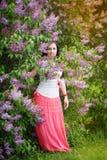 Schöne junge Frau nahe der blühenden Flieder Stockbild