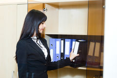 Schöne junge Frau nehmen einen Ordner mit Dokumenten vom Kabinett Stockfoto
