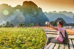 Schöne junge Frau nimmt den Reisenden auf Ländern eines Handys Lizenzfreie Stockfotos