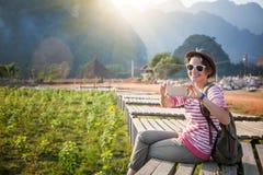 Schöne junge Frau nimmt den Reisenden auf Ländern eines Handys Lizenzfreies Stockfoto