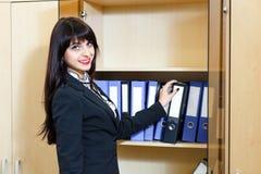 Schöne junge Frau nimmt einen Ordner mit Dokumenten vom Kabinett Lizenzfreie Stockfotos