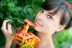 Schöne junge Frau riecht Blumen in einem Garten Lizenzfreie Stockfotografie