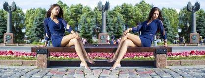 Schöne junge Frau sitzt auf einer Bank Stockfotografie
