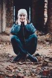 Schöne junge Frau sitzt in den Ruinen auf einem orange Hintergrund in einer Kappe und in einem Schal lizenzfreies stockfoto