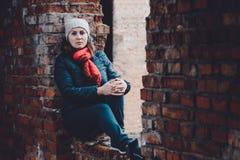 Schöne junge Frau sitzt in den Ruinen auf einem orange Hintergrund in einer Kappe und in einem Schal stockfotografie