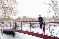 Schöne junge Frau steht auf der Brücke im Winterpark Stockfoto