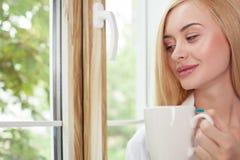 Schöne junge Frau steht auf Fensterbrett still Stockbilder