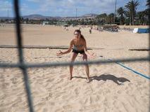 Schöne junge Frau steht am Strandvolleyballfeld Stockbild