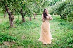 Schöne junge Frau steht zwischen den Bäumen Lizenzfreies Stockfoto