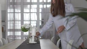 Schöne junge Frau stellt die Tabelle im Wohnzimmer ein stock footage