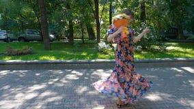 Schöne junge Frau tanzt in einen Park mit einem Blumenstrauß von Blumen stock video footage