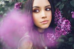 Schöne junge Frau umgeben durch Blumen der Flieder Lizenzfreie Stockfotografie