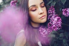 Schöne junge Frau umgeben durch Blumen der Flieder lizenzfreies stockbild