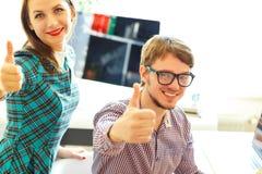 Schöne junge Frau und Mann mit dem Daumen oben im Büro Lizenzfreie Stockbilder