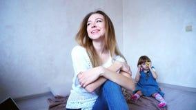 Schöne junge Frau und Mutter, die in camera an lächelt und aufwirft Stockfotos