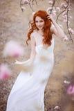 Schöne junge Frau unter dem blühenden Baum lizenzfreie stockbilder