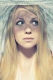 Schöne junge Frau unter einem Schleier Stockbild