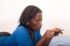 Schöne junge Frau unter Verwendung der Handyspielspiele lizenzfreie stockfotografie