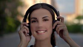 Schöne junge Frau unter Verwendung des intelligenten Telefons, Schreibenmitteilungen, hörend Musik, trinkender Kaffee beim Gehen  stockbilder