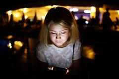 Schöne junge Frau untersucht das Telefon ihr Gesicht wird durch das Licht vom Telefon beleuchtet das Porträt wurde nachts gemacht stockfotografie
