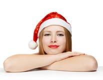 Schöne junge Frau in Weihnachtsmann-Hut, der auf dem Tisch ISO legt Stockfotografie