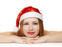 Schöne junge Frau in Weihnachtsmann-Hut, der auf dem Tisch ISO legt Stockbilder