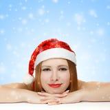 Schöne junge Frau in Weihnachtsmann-Hut, der auf dem Tisch legt Stockfotos