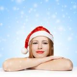 Schöne junge Frau in Weihnachtsmann-Hut, der auf dem Tisch legt Stockbilder