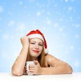 Schöne junge Frau in Weihnachtsmann-Hut, der an den Tabelle wi sitzt Stockfotografie