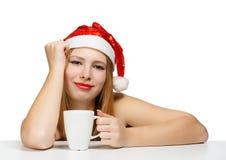 Schöne junge Frau in Weihnachtsmann-Hut, der an den Tabelle wi sitzt Stockbild