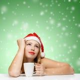 Schöne junge Frau in Weihnachtsmann-Hut, der am Tabellenesprit stationiert Stockbilder